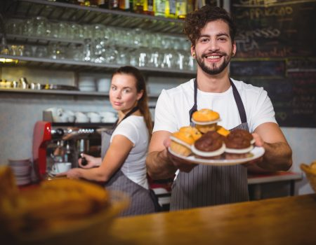 Portrait of waiter holding a plate of cup cake at counter in café